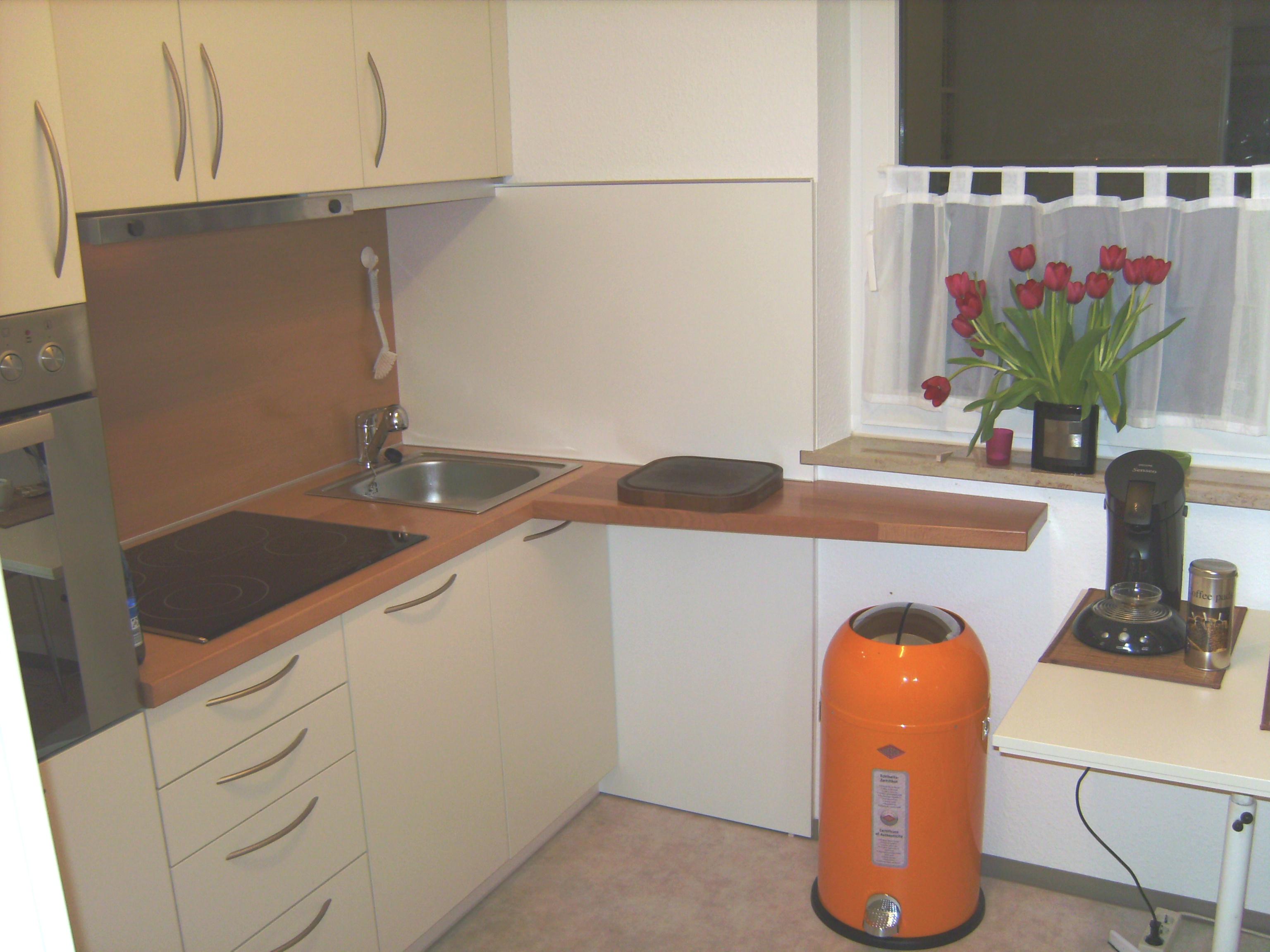 Küche in gelb mit Buchenplatte und Spritzschutz